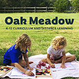 Image of two girls coloring with crayons on a blanket in a field with text Oak Meadow K-12 curriculum and distance learning